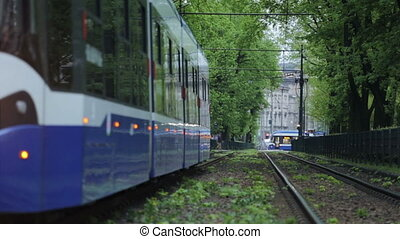Blue tram going through green alley. - Blue tram going...