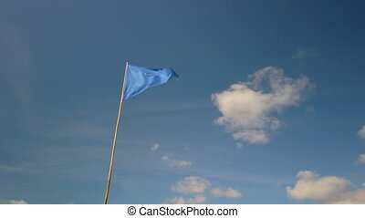 Blue triangle flag fluttering in the wind against blue sky at a beach in France. It indicates a bathing area.
