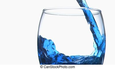 Blue trickle in super slow motion flowing in a glass