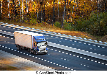 Blue truck on the road in autumn