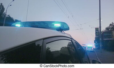 """Blue twirling lights of police car, city road accident,..."