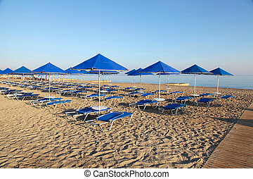 Blue umbrellas and chaise longue on empty sandy beach, Greece
