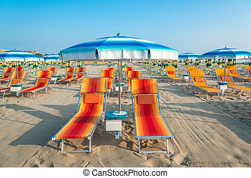 Blue umbrellas and chaise lounges on the beach of Rimini in...