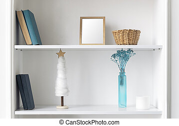 Blue vase, frame and books on white shelves. Classic blue Home accessories and books on wall shelves