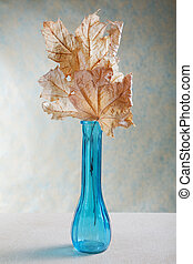 blue vase with dry yellow leaves