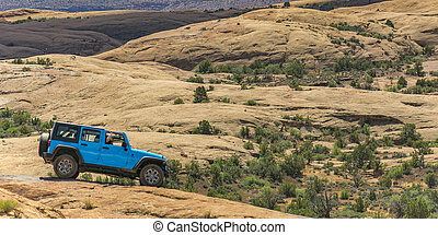 Blue vehicle on a rugged terrain in Moab, Utah. Two people ...