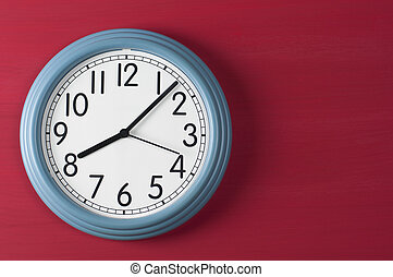 Blue wall clock on red grunge background.