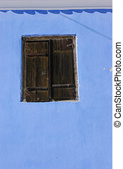 Blue wall with a wooden window