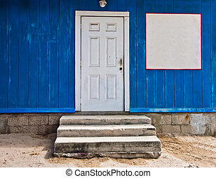 Blue Wall with White Door and Blank white sign