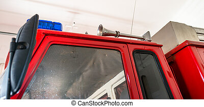 Blue warning signals and a siren placed on the roof of a fire truck.