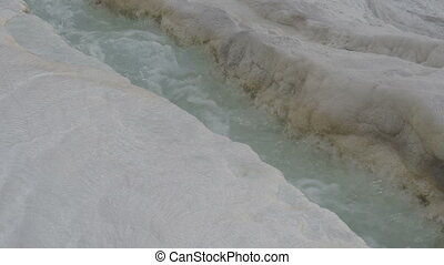 blue water flows down stream in travertine in Pamukkale.