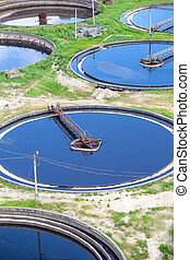 Blue water in an industrial wastewater treatment circular settlers, aerial view