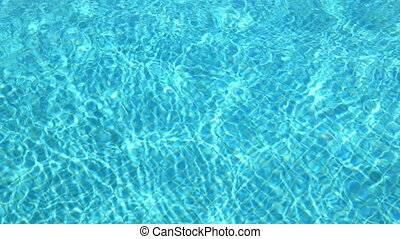 Blue water in swimming pool. Waves and patches of sunlight...