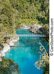 Blue water lake with suspension bridge in tropical jungle