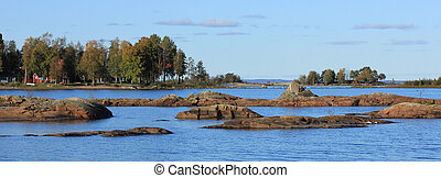 Blue water of Lake Vanern, rock formations and trees on the shore.
