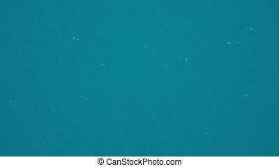 Blue water texture glinting sunlight off of surface. -...