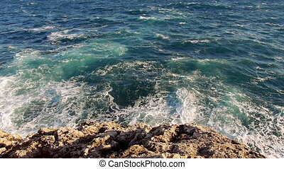 Blue water waves and a rocky beach