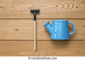 Blue watering can and garden rake on a wooden background.