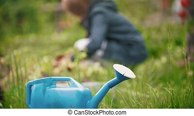 Blue watering can, in the background a girl sitting digs up...