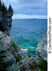 A rocky cliff overlooking blue waters.