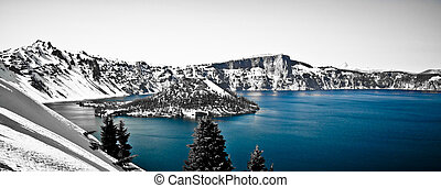The blue water of crater lake, oregon, while there is snow covering the mountainsides all around.