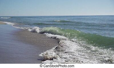 waves roll into the coast in slow motion - Blue waves roll...