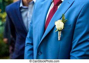 Blue wedding boutonniere on Groom's jacket