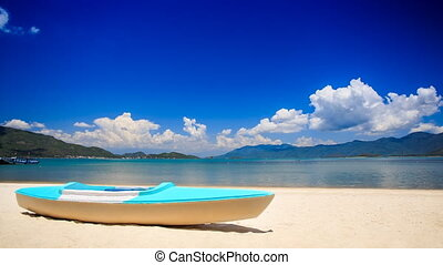 blue white metal paddle boat on gold sand by azure sea beach...