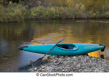 blue whitewater kayak on a rocky shore against river with...