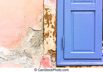 Blue window shutter on old shabby pink wall