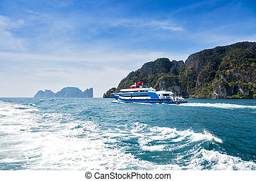 Blue with white and red accents pleasure speed boat. Sailing on the sea against a tropical island. Rear view. Motor track and waves on the water.