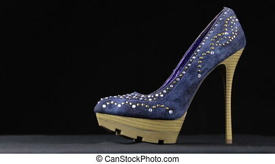 Blue women's high-heel shoes against black background. Slider shot. Shoes made of denim decorated with rhinestones