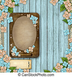 Blue wooden background with a frame, flowers, pearls and lace