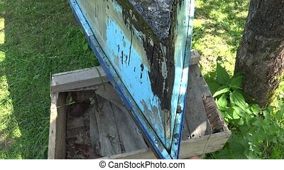Blue wooden boat and young man lay hot tar with gas burner...