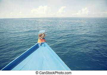 blue wooden boat cruising over deep sea