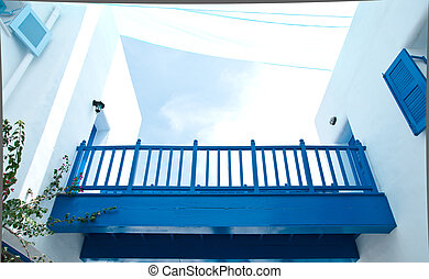 Blue wooden bridge with white mediterranean building