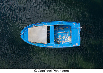 blue wooden fishing boat anchored in the sea, top view