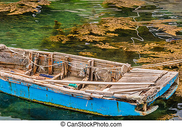 Blue wooden row boat floating on water