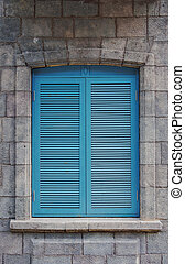Blue wooden shutters on rustic stone wall.