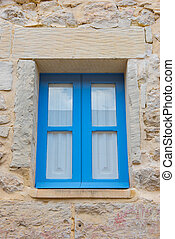 Blue wooden window in a stone house