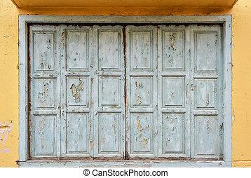 Blue wooden window on yellow wall