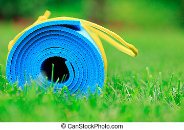 Blue yoga mat on green grass, close up photo, fitness concept