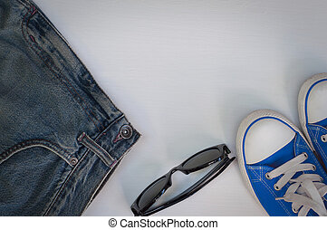 Blue Youth sneakers with glasses on a white wooden background