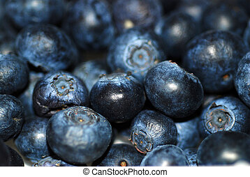 A close up photograph of a punnet of fresh blueberries