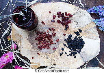 Blueberries and cranberries on wooden board with pattern