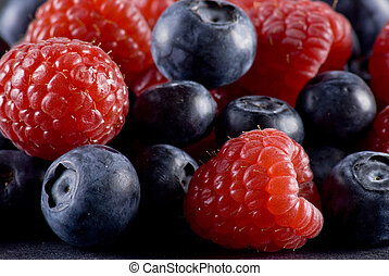 Closeup of fresh blueberries and raspberries mixed toghether