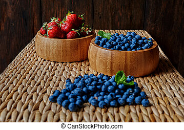 blueberries and strawberries on a rattan table