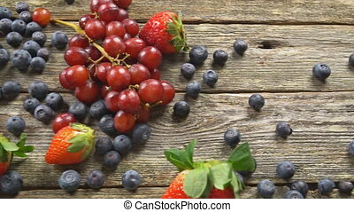 Blueberries Grape Strawberries with wooden on wooden table...
