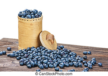 Blueberries in a basket is scattered on the wooden