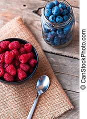 Blueberries in a jar and raspberries in a wood bowl on top of burlap with a wooden table top